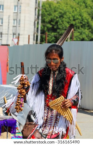 PERM, RUSSIA - JUNE 21, 2014: Man of Camuendo Wuambrakuna Indian band performs on street  - stock photo