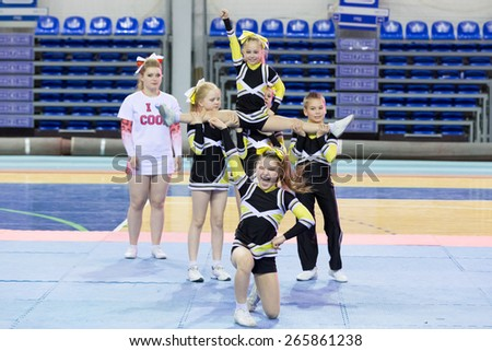 Perm, Russia - March 28, 2015. Championship Perm Krai on cheerleading. Girl in black yellow suit sitting on  splits in  hands of team in group stunt - stock photo