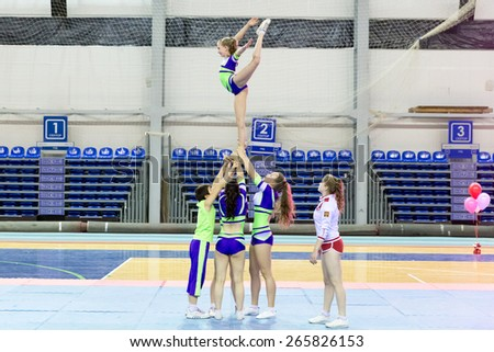 Perm, Russia - March 28, 2015. Championship Perm Krai on cheerleading. Girl in blue green suit making element Nike