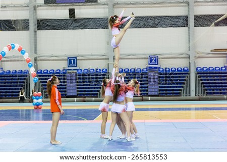 Perm, Russia - March 28, 2015. Championship Perm Krai on cheerleading.  Girl in pink white suit makes Heel Stretch in  group stunt