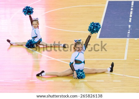 Perm, Russia - March 28, 2015. Championship Perm Krai on cheerleading. Girls in white and blue suits with pompons  doing  splits on  floor