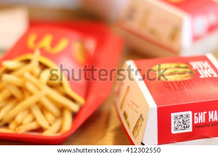 PERM, RUSSIA - MAY 15, 2015: (shallow dof) French fries, Big Mac in McDonalds restaurant. McDonalds Corporation - US corporation, large network of fast-food restaurants, working on franchise system - stock photo