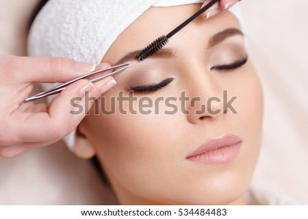 eyebrow tweezing. beautiful young woman gets eyebrow correction procedure. tweezing her eyebrows n