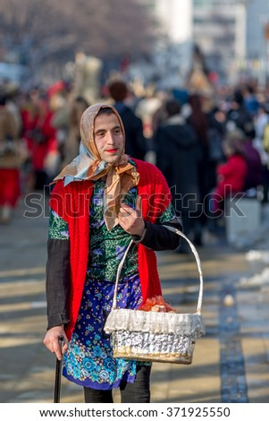PERNIK, BULGARIA - JANUARY 30, 2016: Young male, dressed as female in a colorful costume, carrying a basket and leaning on a cane at Surva, the International Festival of the Masquerade Games
