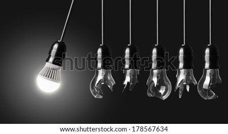 Perpetual motion with broken light bulbs and LED bulb - stock photo