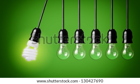 Perpetual motion with light bulbs and energy saver bulb. Idea concept on green background. - stock photo