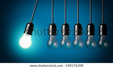 Perpetual motion with light bulbs. Idea concept on blue background. - stock photo
