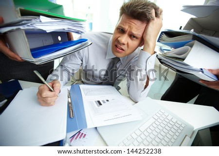 Perplexed accountant looking at camera while doing financial reports