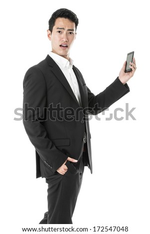 Perplexed businessman using a smart phone - stock photo