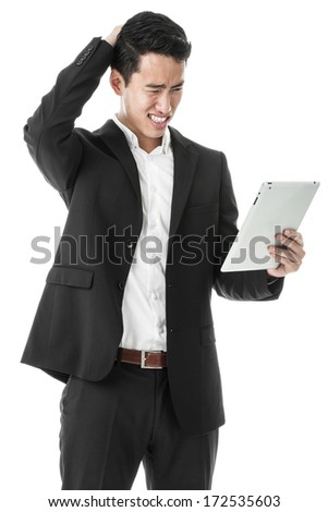 Perplexed businessman using a tablet