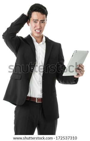 Perplexed businessman using tablet - stock photo