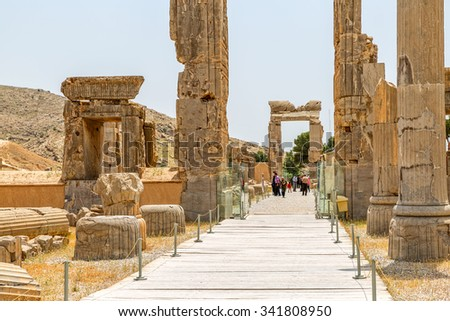 PERSEPOLIS, IRAN - MAY 3, 2015: People walking by the ruins of old stone gates, a capital of the Achaemenid Empire 550 - 330 BC.