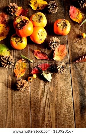 Persimmon,fall leaves and pine cone.image of autumn.