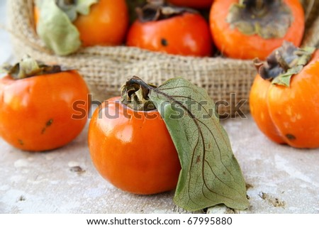 Persimmon on a wooden table with a bag in the background - stock photo