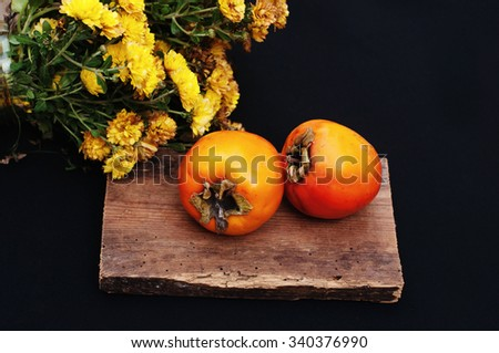 Persimmonon black  background. Fresh organic persimmon. Fresh persimmon on  black kitchen table. persimmon isolated on black.  Fresh fruits. Organic persimmon. Sweet.  Food. Bouquet  chrysanthemums. - stock photo