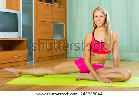 Persistent happy young woman doing yoga at home and smiling  - stock photo