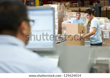 Person At Computer Terminal In Distribution Warehouse - stock photo