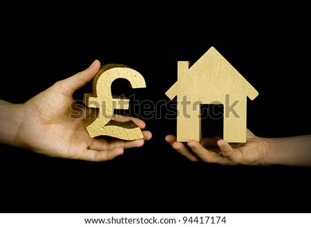 person buying a house with english pounds, black background - stock photo