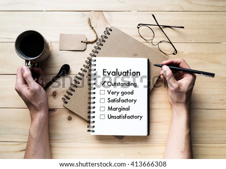 Person checking excellent mark in Evaluation check box on notebook (Business concept)  - stock photo