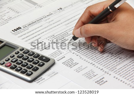 Person completing 1040 tax form with calculator