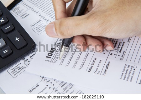 Person completing 1040 tax form with calculator and pen - stock photo