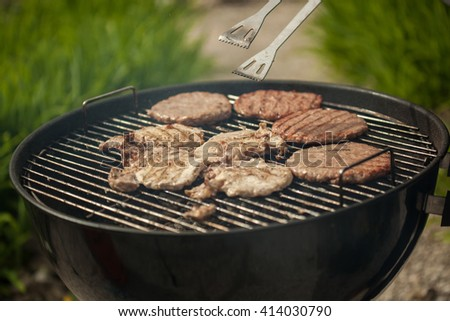 Person cooking steaks on a BBQ grill