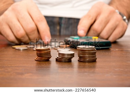 Person counting money using a calculator - stock photo