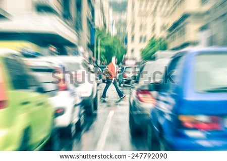 Person crossing the road during rush hour in Cape Town - Concept of connection between people and traffic jam on a vintage filtered look - Radial zoom defocusing of commuter cars on urban city streets - stock photo