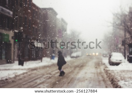 Person crossing the street during a snow storm. - stock photo