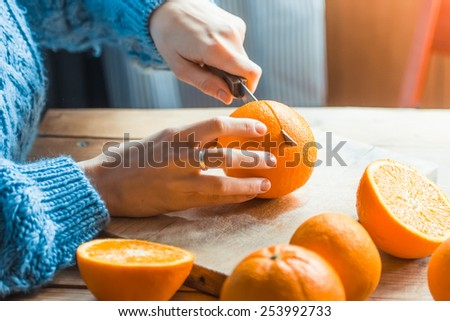 Person cutting fresh oranges on wooden table