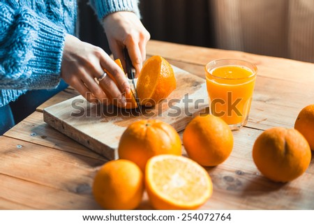 Person cutting  to make juice from fresh oranges on wooden table. Selective focus point on cutted orange - stock photo