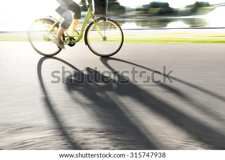 Person cycling along river in bright sunshine, casting long shadow on cycling path - stock photo