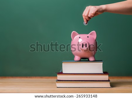 Person depositing money in a pink piggy bank on top of books with chalkboard in the background as concept image of the costs of education  - stock photo