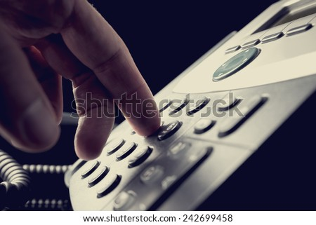 Person dialing out on a telephone punching in the numbers on the keypad with a finger, vintage effect toned image. - stock photo
