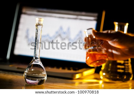 person doing chemical research and holding a beaker - stock photo