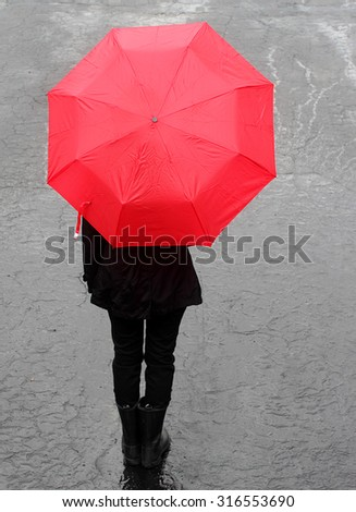 Person dressed in black holding red umbrella after the rain - stock photo