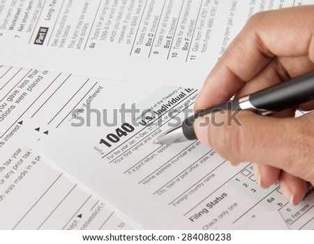 Person filing federal income tax form before deadline - stock photo