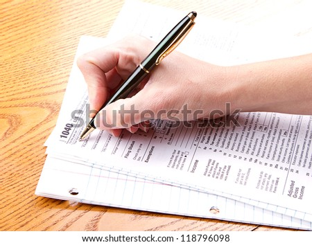 Person filling out a 1040 tax form - stock photo