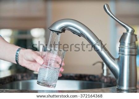 person filling up a glass of tap water - stock photo