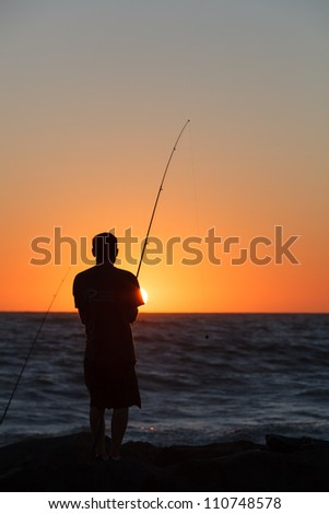 Person fishing on rocks at sunset