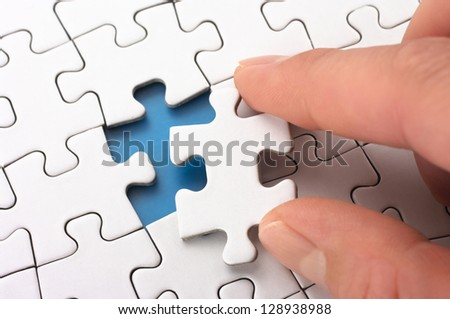 Person fitting the last puzzle piece.Concept image of building and button up. - stock photo