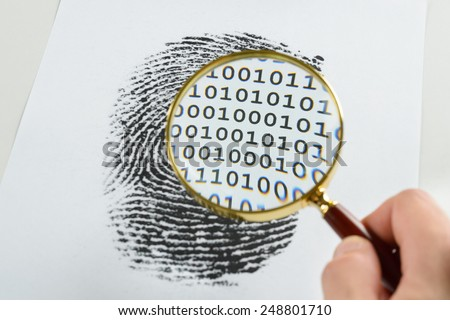 Person Hand With Magnifying Glass Over A Finger Print Revealing Binary Code Within The Print - stock photo