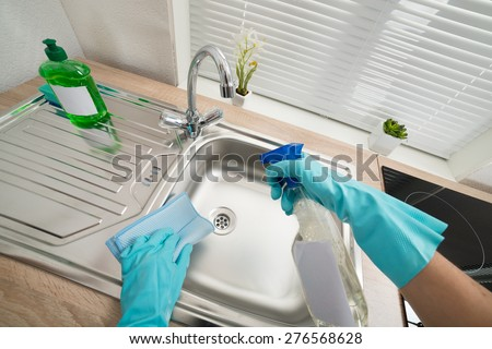 Person Hands In Blue Glove Cleaning Silver Kitchen Sink - stock photo