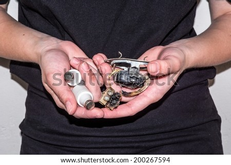 Person holding a damaged electric socket and two electric fuses in her hands