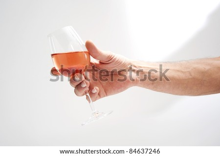 Person holding a glass of rosé wine