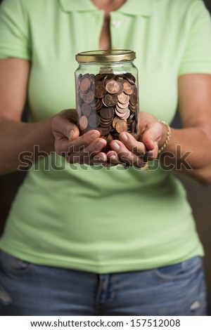Person holding a jar full of pennies meaning tips or savings. - stock photo