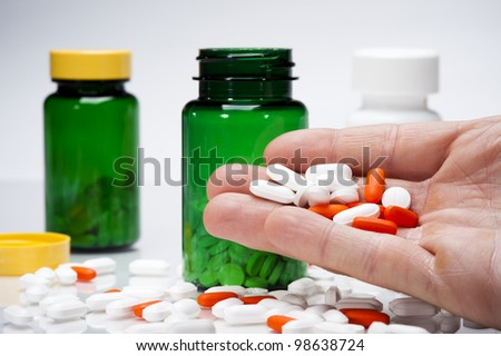 person holding a variety of pills and vitamins