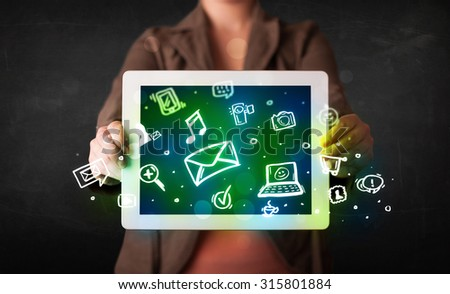 Person holding a white tablet with media icons and symbols - stock photo