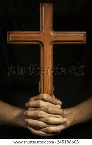 Person holding a wooden cross, symbolizing religious man - stock photo