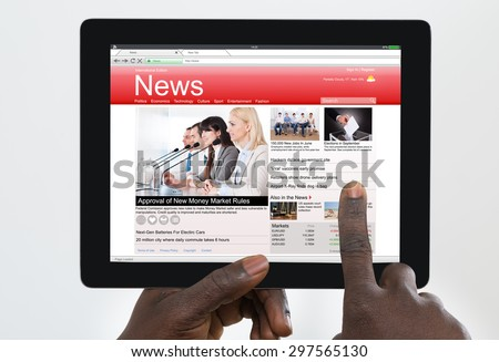 Person Holding Digital Tablet With News On Screen - stock photo